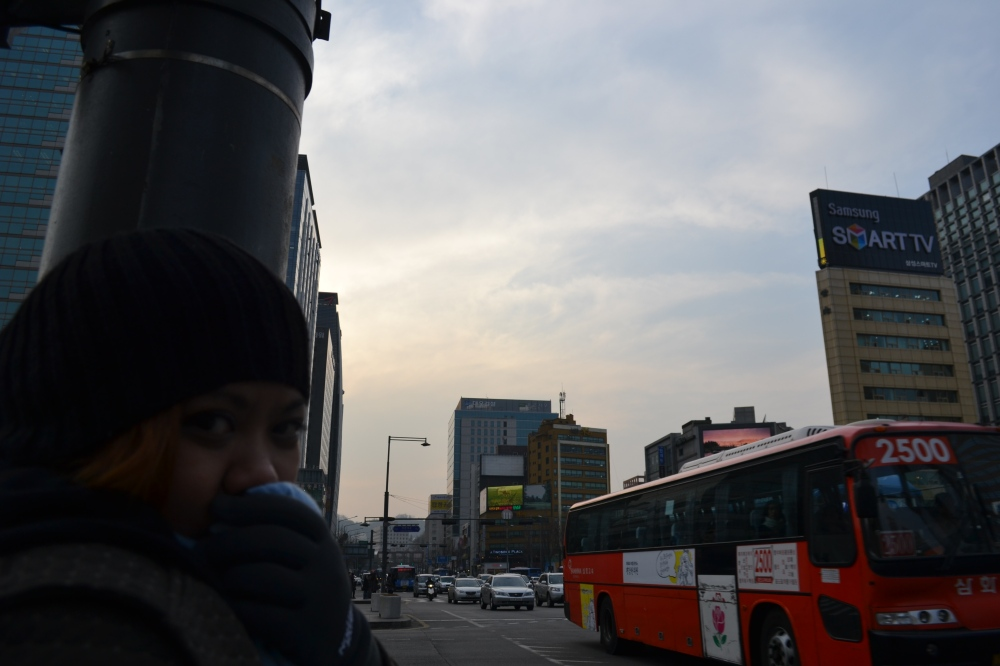 A bus in Seoul plying near the King Sedong monument and near the Seoul Police Station